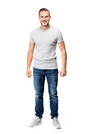 Handsome man in a white t-shirt, looking cheerful, smiling straight into the camera. Full body studio shot.