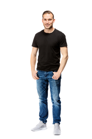 Casual, relaxed man in a black t-shirt, looking straight into the camera. Isolated on white background. Full body shot.