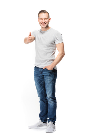 Positive handsome man, showing okay gesture, looking confidently at the camera. Full body studio shot.