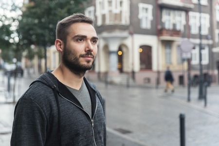 A portrait of a man in the city, standing on the street with people passing by.