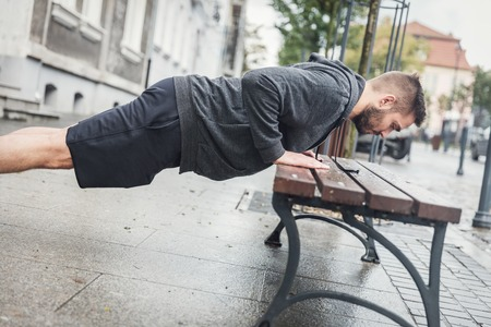 Man doing push-ups on a city bench. Sporty routine of millenial generation.