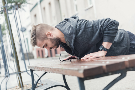 Outdoor training in the city using street objects. Workout routine. Stock Photo