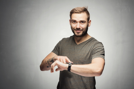Handsome man pointing at a watch on the wrist. It's time concept