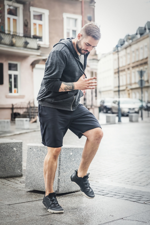 Young man warming up on a city street. Healthy lifestyle. Jog trot