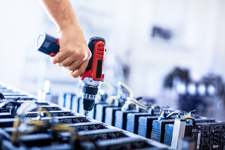 Assembling bitcoin mining machines. Mans hand screwing. Cryptocurrency farm. E-business. Stock Photo