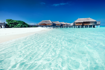 Fancy summer hotel with houses standing on stakes in the water. Clear blue water and beach on Maldives
