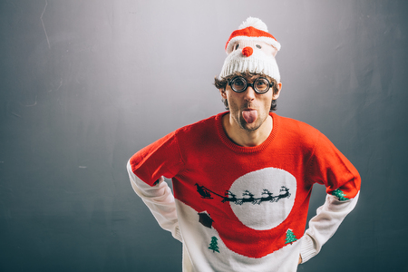 Moody man sticking his tongue out, dressed in funny glasses, christmas sweater and beanie.