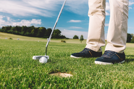 Man playing golf, trying to aim golfball into the hole. Sports activity.