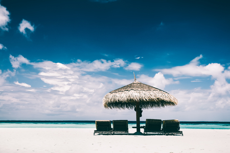 Straw umbrella with sunbeds underneath placed on a sandy beach by the ocean. Tropical vacation on Maldives