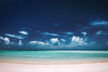 Sandy beach, clear see-through sea and blue sky. Tropical landscape. Seashore view, Maldives