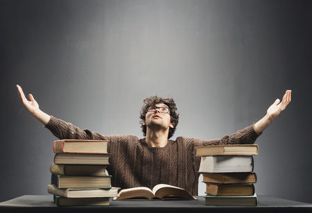 Young man sitting in front of desk full of book, spreading his hands helplessly. College student concept. Stock Photo