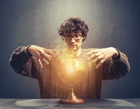 Young man gazing at the glowing crystal ball. Predicting the future. Crystal gazing. Magic. Stock Photo