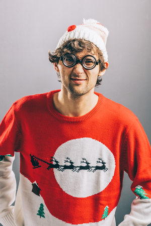 Grumpy man in funny glasses, christmas sweater and beanie looking pouty. Banque d'images