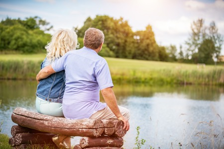 Older marriage sitting together on a bench by the lake. Retirement activities. Happy mature couple. Stockfoto
