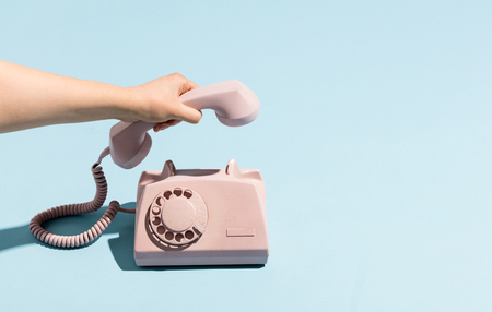 De hand die van de vrouw een retro telefoonontvanger neerlegt, die omhoog hangt. Pastelkleuren. Blauw en roze.