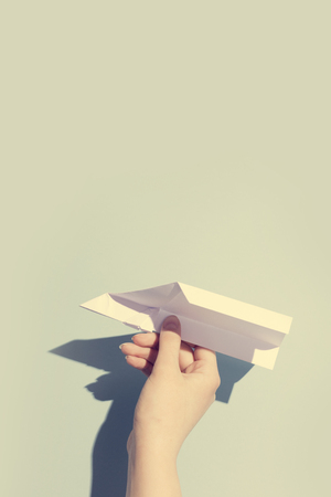 Woman's hand playing with white paper plane. Aircraft. Dreams concept. Standard-Bild