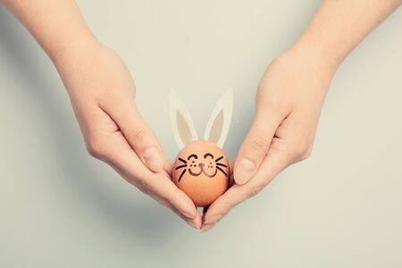 Womans hand holding an Easter bunny made from an egg. Traditional holiday. Christianity