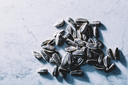 A few black sunflower seeds on a light marble background. Fit snacks. Nutrition.