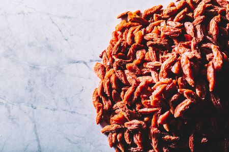 Little red dried goji berries on a pile. Superfoods. Healthy snacks. Dieting and healthcare.
