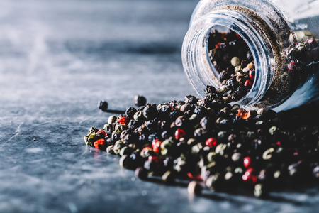 Multicolored grains of pepper spilling out of transparent glass jar. Natural seasoning.