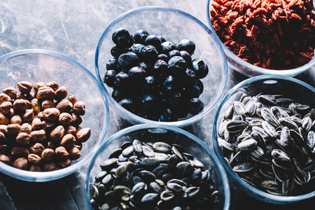Five bowls with Brasilian nuts, blueberries, goji berries, pumpkin and sunflower seeds. Superfoods. Stock Photo