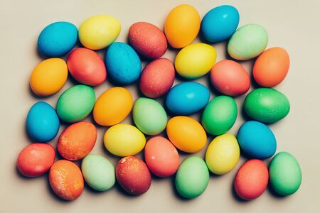 Bunch of colorful eggs on a creamy background. Easter traditions. Stock Photo
