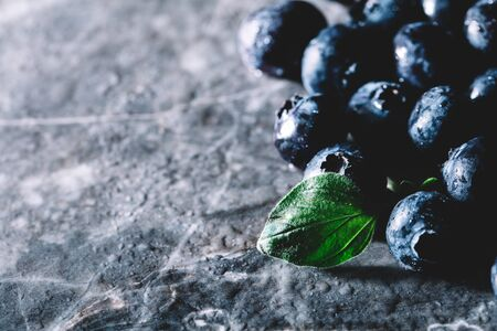 Fresh juicy blueberries and a green leaf laying on a dark kitchen counter. Healthy snacks. Copyspace Stock Photo