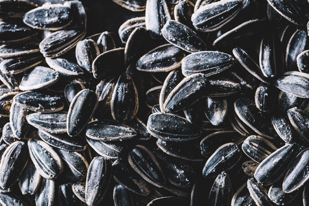 A pile of little black sunflower seeds. Healthy snacks. Diet and healthcare.