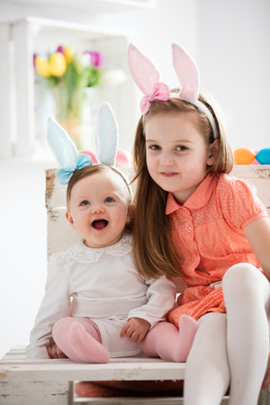 Two sisters in funny bunny costumes sitting together. Sibling bond. Easter celebration.