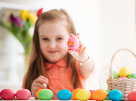 Young girl showing a hand-made egg with a chicken drawing on it. Easter traditions.