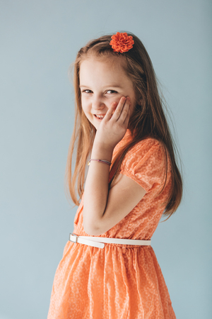Carefree young girl in a cute orange dress, smiling and laughing. Happy kid.