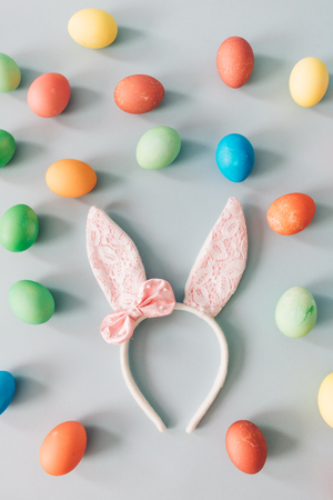 Furry headband with pink bunny ears laying on the floor, surrounded by colorful dyed eggs. Easter. Stock Photo