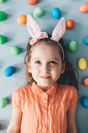 Cute young girl with pink bunny ears laying on the floor, surrounded by colorful eggs. Easter.