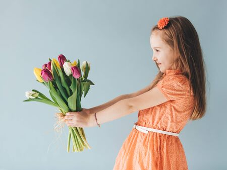Young child holding a bunch of freshly cut flowers. Celebrating a birthday