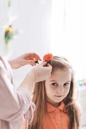 Mother clipping a hair clip with red flower. Parenthood concept. Family love.