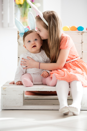 Older sister kissing her younger sibling, both in funny headbands with rabbit ears. Easter. Stock Photo