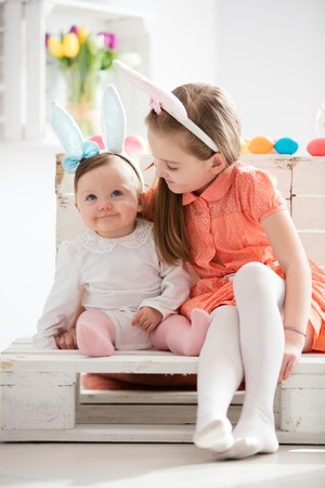 A little girl and her older sister in bunny ears headbands sitting together.