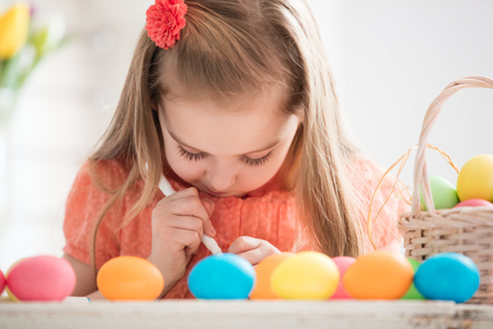 Focused child creating drawings on colorful dyed eggs. Easter traditions and preparations.