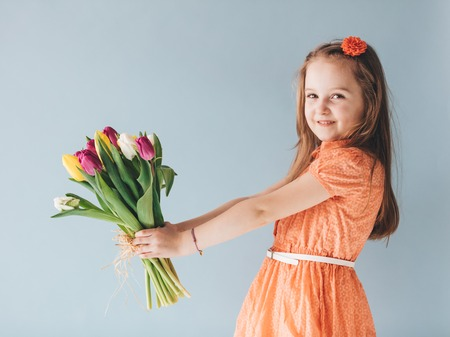 Little girl holding a bunch of colorful tulips. Mothers day gift. Valentines day. Stock Photo