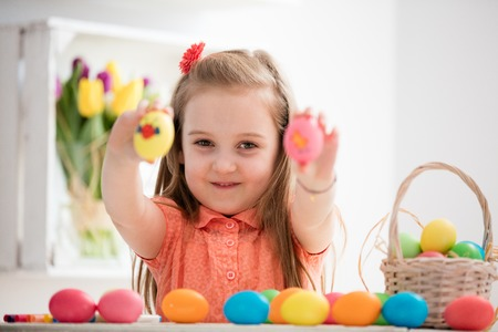 Little girl showing her hand-painted colorful eggs. Easter eggs. Holiday traditions.