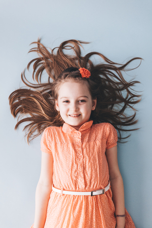 Young girl with messy hair laying down on the floor, smiling. Cheerful child.