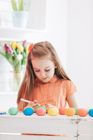 Young focused girl drawing patterns on dyed eggs. Easter traditions and celebration. Stock Photo