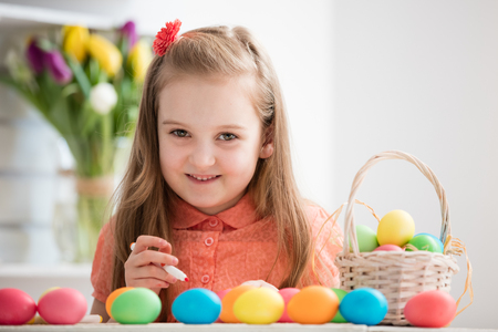 Young girl painting eggs by the desk, smiling. Easter eggs. Christian traditions.
