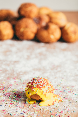 Yellow doughnut decorated with sugar strands laying on a kitchen counter.