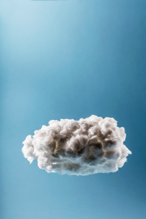 Single cloud on a light blue background. Weather or digital cloud concept. Cotton handmade. Stock Photo