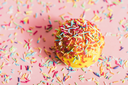 Doughnut with yellow icing and colorful sprinkles on a sprinkled pink background.