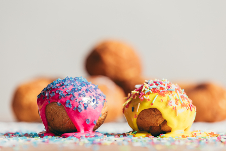 Two colorful decorated doughnuts laying on a table. Homemade bakings.