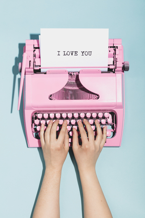 Womans hands writing I love you on an oldschool pink typewriter. Valentines day. Stock Photo