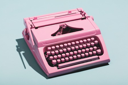 Pink typewriter on a blue pastel background. Vintage machine. Journalism. Stock fotó