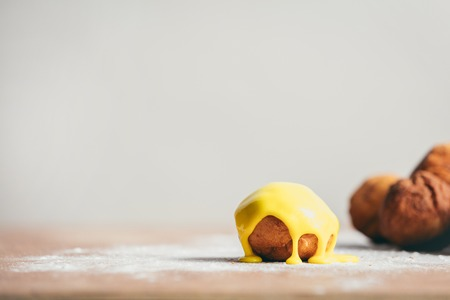 Little round donut with yellow icing on the kitchen counter. Home-baked snack. Stock Photo